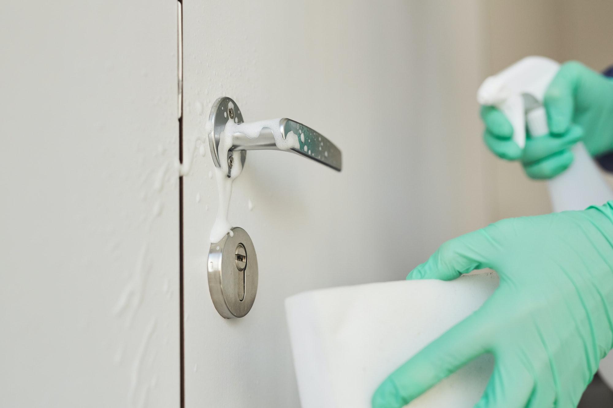 Worker Disinfecting Door Handle Close Up